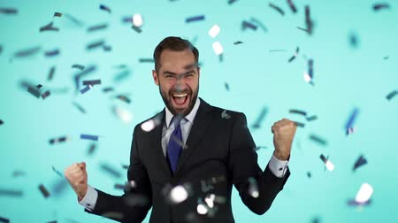 evet : Excited businessman champion guy celebrating winning under confetti rain. He shows yes gesture of victory. Happy ecstatic man screaming of joy.