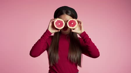eye piece : Portrait of young beautiful woman in red with two half of juicy grapefruit on pink studio background. Healthy eating, dieting, antioxidants concept