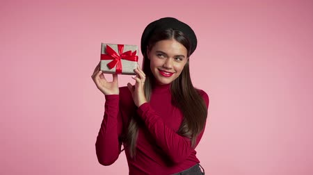 африканского происхождения : Excited woman received gift box with bow. She is happy and flattered by attention. Girl on pink background. Studio footage.