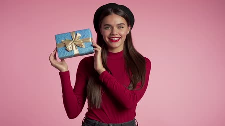африканского происхождения : Beautiful young woman with perfect makeup holding blue gift box with bow on pink wall background. Girl smiling, she is happy to get present. Стоковые видеозаписи