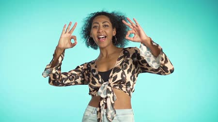 três quarto comprimento : Young woman making OK sign over blue background. Winner. Success. Positive young african girl in leopard print top smiles to camera Vídeos