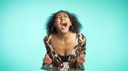 alta calidad : Close up of a young african american stressed afro girl shouting isolated over blue background. Slow motion. Stressed and depressed woman in leopard clothing