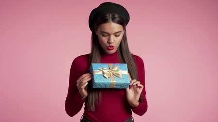 африканского происхождения : Joyful beautiful woman with perfect makeup holding blue gift box with bow on pink wall background. Trendy girl smiling, she is glad to get present.