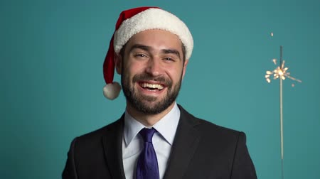 fire suit : Portrait of handsome businessman in suit and Santa hat with bengal sparkler fire isolated on blue studio background. Young happy man with beard celebrate Christmas or New year party.