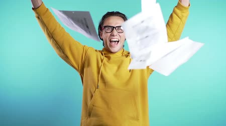 him : Young man in glasses throwing papers documents into air and celebrates success on blue background. Freedom, successful completion of project concept.