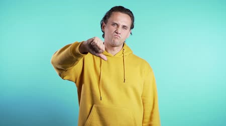 perdedor : Young man standing on blue studio background expressing discontent and showing thumb down gesture at camera. Portrait of guy with sign of dislike.