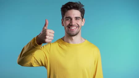 čtvrtý : Handsome young man in yellow wear smiles to camera. Hipster guy showing thumb up sign over blue background. Winner. Success. Body language. Dostupné videozáznamy