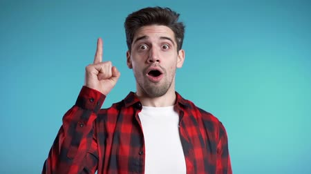 wynalazek : Portrait of young thinking pondering man in red having idea moment pointing finger up on blue studio background. Smiling happy student guy showing eureka gesture. Wideo