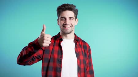 čtvrtý : Positive young man smiles to camera. Hipster guy showing thumb up sign over blue background. Winner. Success. Body language. Dostupné videozáznamy