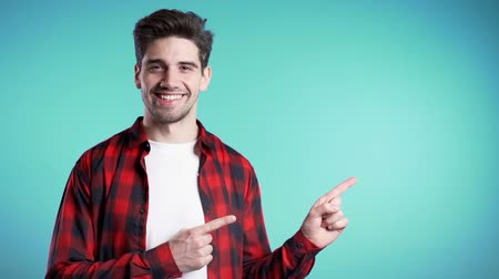 forefinger : Happy smiling man in red wear presenting and showing something isolated on blue background. Stock Footage