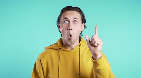жест : Portrait of young thinking pondering man in yellow having idea moment pointing finger up on blue studio background. Smiling happy student guy showing eureka gesture. Стоковые видеозаписи