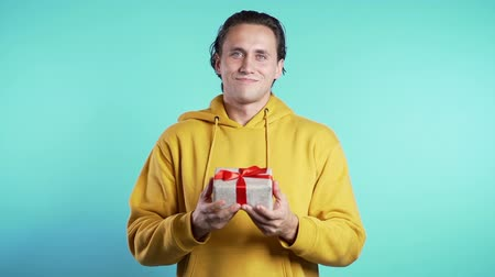 darovat : Handsome man holding christmas or birthday gift box on blue studio background and gives it to camera. He is happy, smiling.
