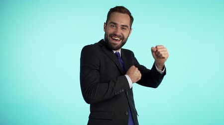 evet : Man shows yeah gesture of victory, he achieved result, goals. Surprised excited happy businessman funny dancing on blue background. Stok Video