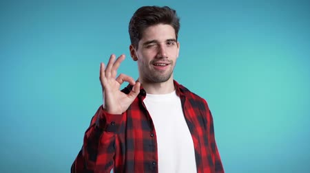 čtvrtý : Positive young man smiles to camera. Hipster guy showing OK sign over blue background. Winner. Success. Body language.