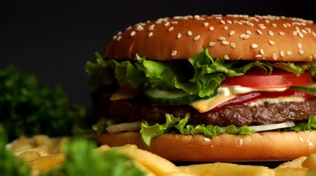 majonéz : Big appetizing burger with meat cutlet, onion, vegetables, melted cheese, lettuce and mayonnaise sauce. Isolated hamburger rotates on dark smoke background, close-up view