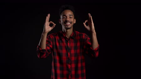 forefinger : Handsome man in red wear on black studio background smiles to camera and gives ok sign. Happy african american guy showing gesture of approval. Winner.Success.