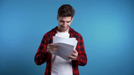 dosya : Young handsome man checks documents, utility bills, report. Businessman isolated on blue background. He is satisfied with work of corporate staff.