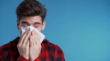 zsebkendő : Young man sneezes into tissue. Isolated guy is sick, has a cold or allergic reaction. Health, medicine, illness, treatment concept