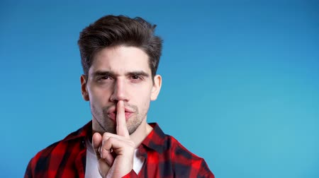 sprakeloos : European handsome man holding finger on his lips over blue background. Gesture of shhh, secret, silence. Copy space