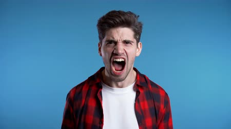 zuřivý : Young european stressed man in red shirt shouting isolated over blue background. Slow motion. Stressed and depressed guy loudly screaming to camera.