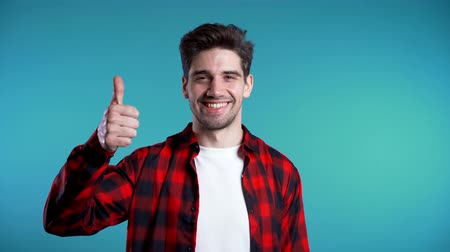 dedo indicador : Positive young man smiles to camera. Hipster guy showing thumb up sign over blue background.