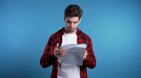 dosya : Serious businessman scatters papers on blue background. He is unsatisfied, anxious and confused with work of staff. Young male office employee checks documents, reports.