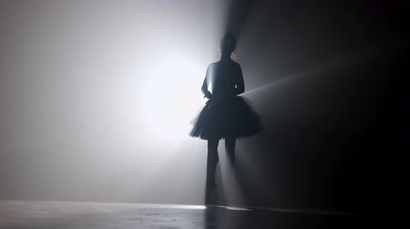 tüt : Professional ballerina dancing ballet in spotlights smoke on big stage. Beautiful young girl wearing black tutu dress on floodlights background. Black and white. Stok Video