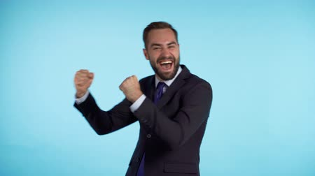 evet : Surprised excited happy businessman funny dancing on blue background. Man shows yeah gesture of victory, he achieved result, goals. Stok Video