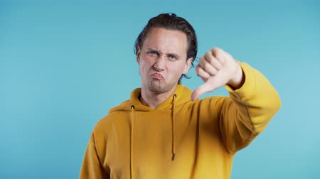 perdedor : Young handsome man standing on blue studio background expressing discontent and showing thumb down gesture to camera. Portrait of guy with sign of dislike. Vídeos