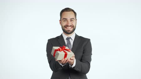 prémie : Handsome businessman in suit gives gift box and hands it to the camera. He is happy, smiling. Man with beard on white background. Positive holiday footage