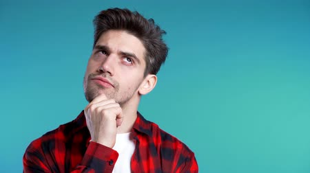 doubt : Copy space.Thinking man looking up and around on blue background. Worried contemplative face expressions. Handsome male model in red shirt. Stock Footage