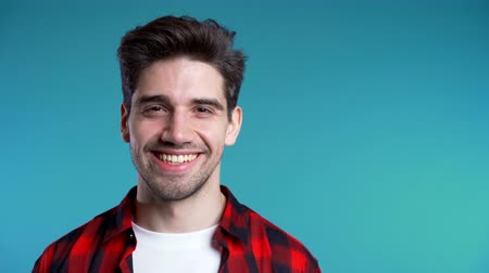 galhofeiro : Handsome european man with trendy hairdo in red plaid shirt on blue studio background. Cheerful guy smiling and looking to camera. Vídeos