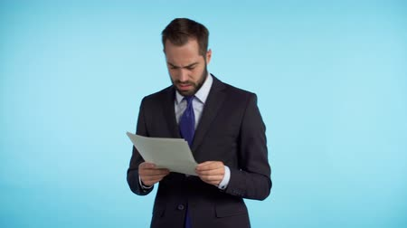 surcharge de travail : Serious businessman boss isolated on blue background studio. Man is unsatisfied with work of staff. Young mature male office employee in suit jacket checking documents, reports