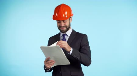 документация : Young engineer businessman in suit jacket checks documents, building project, report. Businessman isolated on blue background as on construction. He is satisfied.