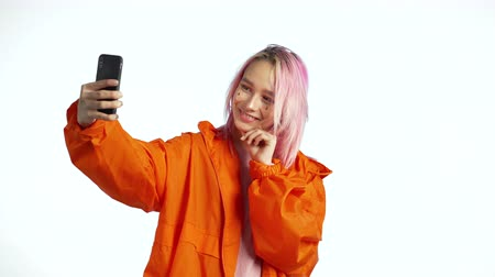 mobile music : Girl with pink hair and extraordinary appearance make selfie on blue background. Using modern technology - smartphone, social networks