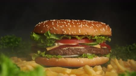 majonez : Big appetizing burger with meat cutlet, onion, vegetables, melted cheese, lettuce and mayonnaise sauce. Isolated hamburger rotates on dark smoke background, close-up view
