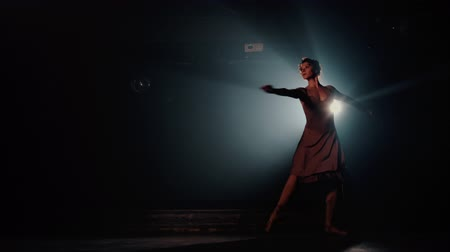 tüt : Ballerina is practicing her moves on dark stage. Young girl dancing in beige dress, spinning around and smiling.