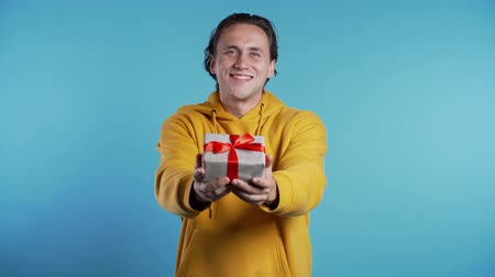 kerstpakket : Handsome man holding christmas or birthday gift box on blue studio background and gives it to camera. He is happy, smiling.