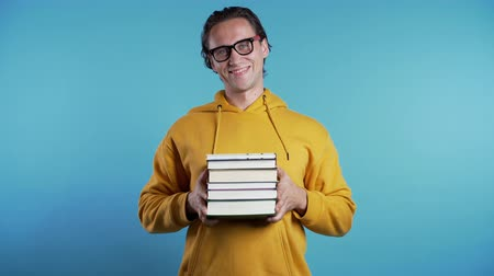 книжный шкаф : European student in yellow hoodie on blue background in studio holds stack of university books from library. Guy smiles, he is happy to graduate. 4k Стоковые видеозаписи