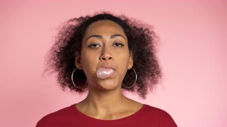 goma : Playful girl in red wear blows bubblegum, chewing gum in slow motion. Pretty african american woman stands on pink background.