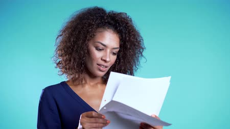 하강 : Pretty african american female boss checks documents, utility bills. Serious businesswoman standing on blue background.