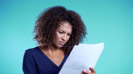 pozdravit : Serious african woman is unsatisfied with papers, bills, documents or reports on blue background.