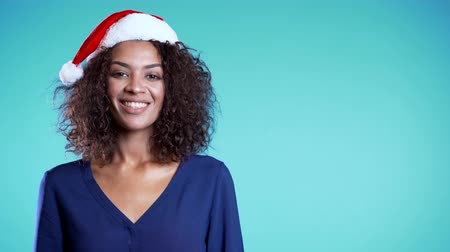 különc : Copy space. Attractive mixed race girl in Santa hat celebrating Christmas or New year on blue background.