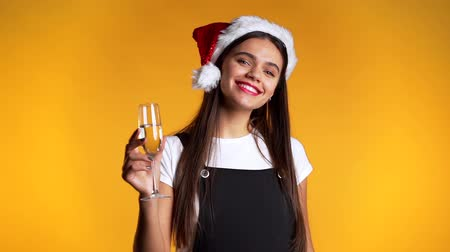 kırmızı şarap : Young cute girl smiling and holding glass of champagne or wine on yellow studio background. Woman in Santa hat. New year mood Stok Video