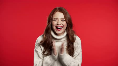 yalıtılmış : Surprised excited happy woman. Portrait of beautiful young girl with ecstatic face expressions, she claps hands. Female shocked model on red background.