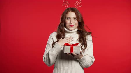 krans : Young cute girl smiling and holding present box on red studio background. Woman in Christmas head wreath - deer horns. New year mood.