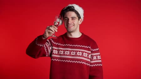 kırmızı şarap : Handsome man smiling and holding glass of champagne or wine on red studio background. Guy in Santa hat. New year party 2020 mood