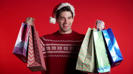 kerstpakket : Handsome young man in Christmas sweater and Santa hat holds shopping paper bags on red studio background. Guy bought presents on sales with discounts.