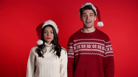 recitazione : Amazed european man and woman shocked, saying WOW. Young couple in Santa hats surprised to camera over red background. Filmati Stock