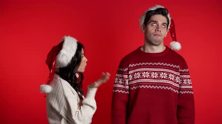 argumento : Young woman in Christmas hats emotionally scolds her boyfriend on red background in studio. Bored man rolling his eyes. Concept of conflict, problems in relationships.